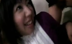 Two Asian gals sit on the couch and are exposed to a couple