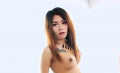 Sexy Thai ladyboy masturbates her hard cock on the bed